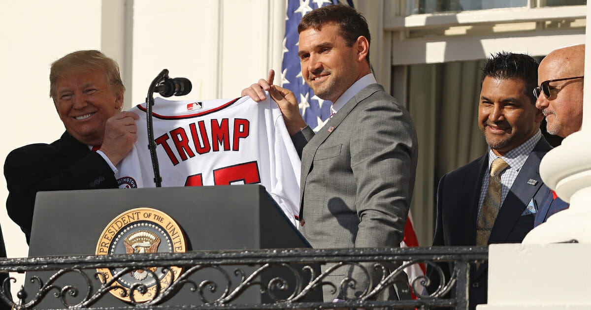 Washington Nationals first baseman Ryan Zimmerman presents President Donald Trump with a team jersey during a celebration of the 2019 World Series champions at the White House on Nov. 4, 2019, in Washington, D.C.