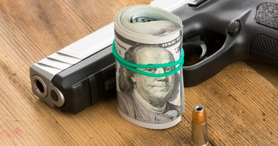 Handgun with a roll of 100 dollar bills and a single bullet lying on a wooden surface.