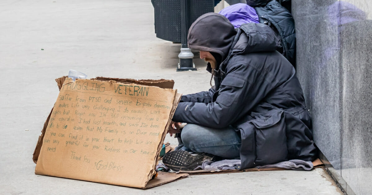 A veteran sits next to a cardboard sign asking for help.