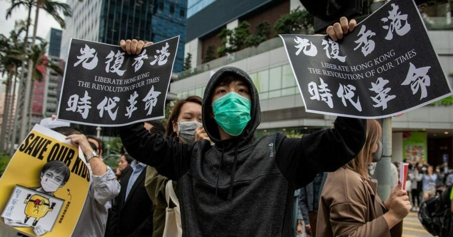 People gather in support of pro-democracy protesters during a lunch break rally in the Kowloon Bay area in Hong Kong on November 26, 2019.