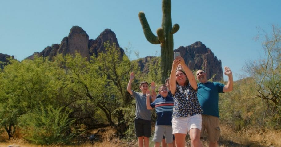 A family takes a photo in front of a cactus in Mesa, Arizona.