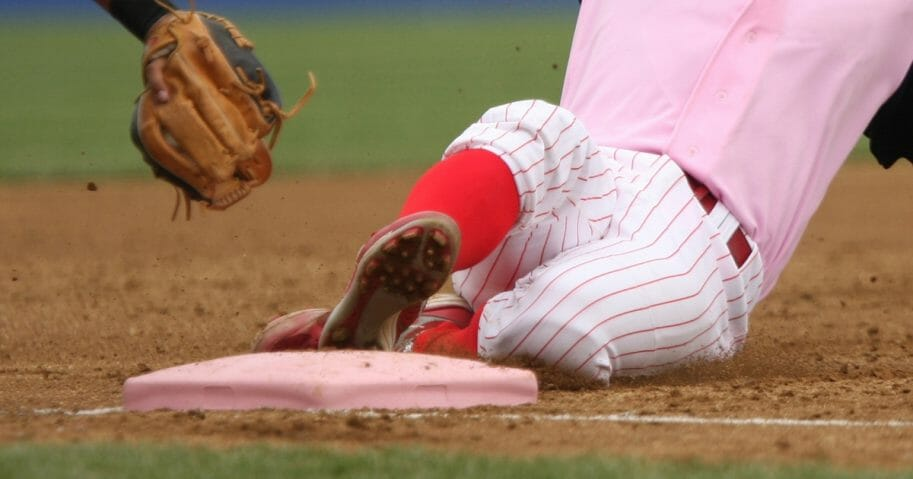 A baseball player slides into third base before the tag.