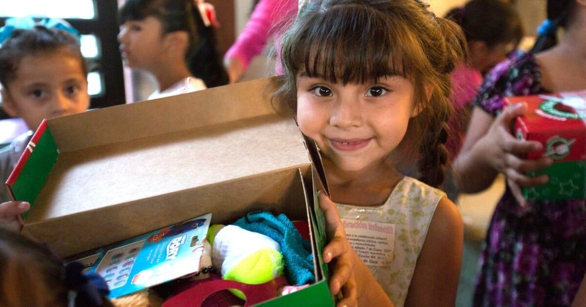A young girl holds up the gift box she received from Samaritan's Purse.