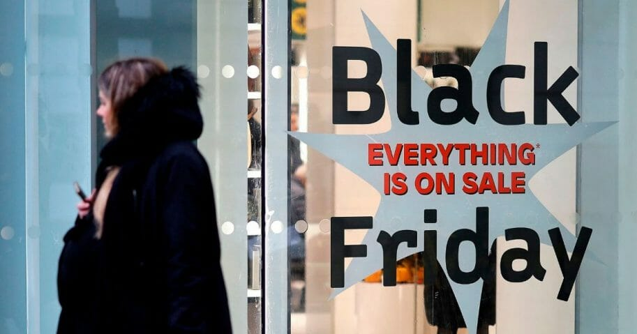 Shoppers pass promotional Black Friday sign in London