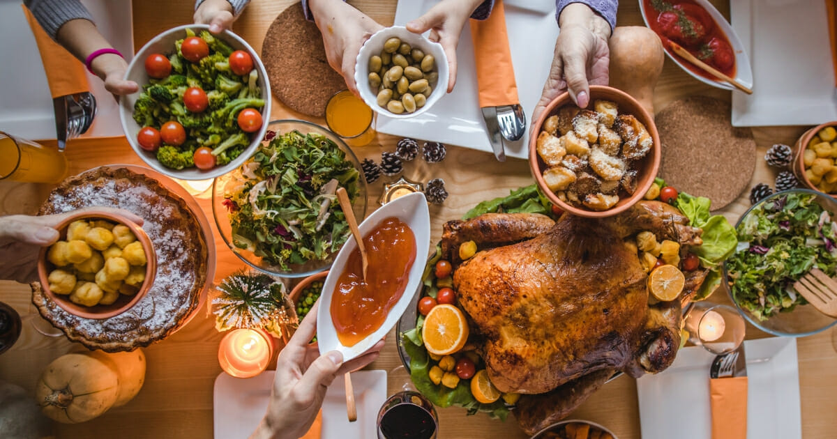 A stock photo of people passing side dishes during Thanksgiving dinner at dining table.