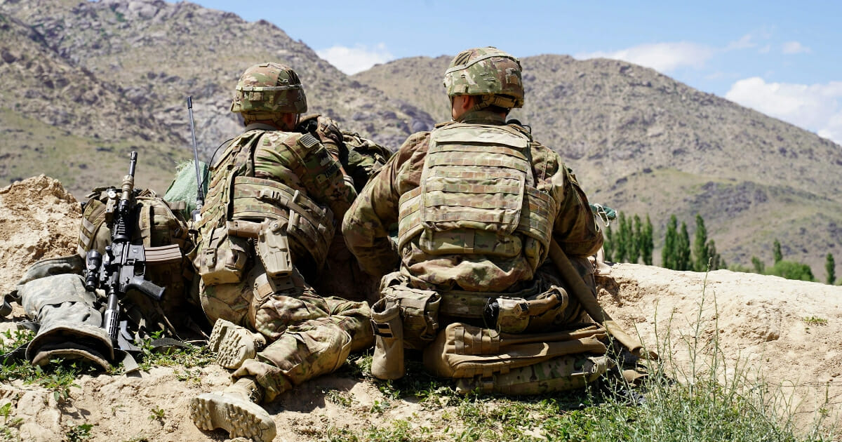 U.S. soldiers look out over the Afghan hillsides at a checkpoint in Nerkh district of Wardak province on June 6, 2019.