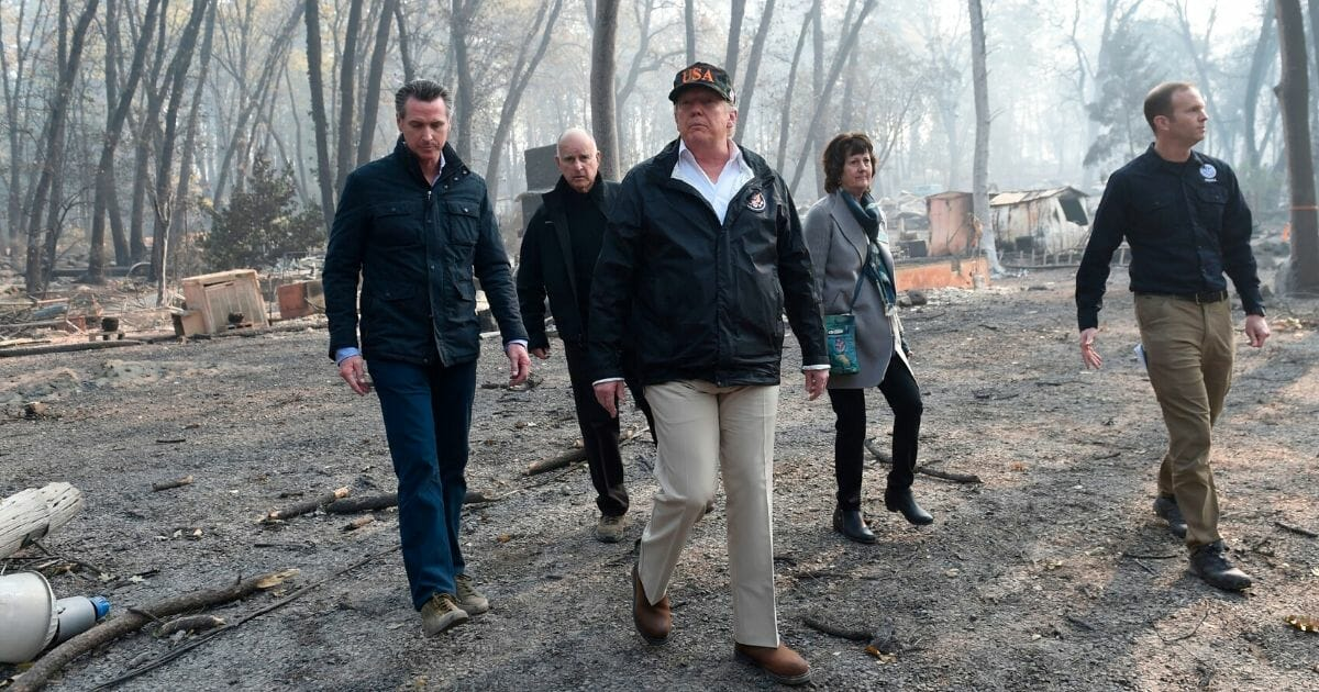 President Donald Trump, center, walks with California government officials as they view damage from wildfires in Paradise, California, on Nov. 17, 2018.