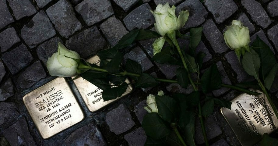 Roses lie on the ground between so-called Stolpersteine, brass stumbling blocks, to commemorate the 75th anniversary of the Kristallnacht pogroms on November 9, 2013, in Berlin.