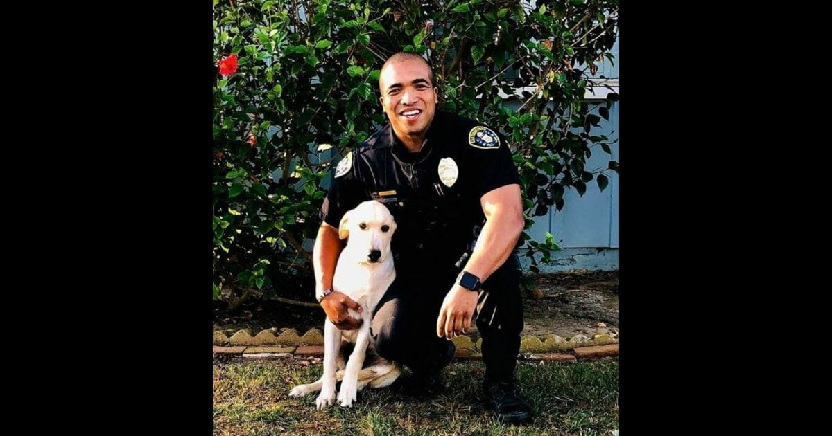 Office Andre Thomas of the San Diego Police Department poses with his new dog, Victor.