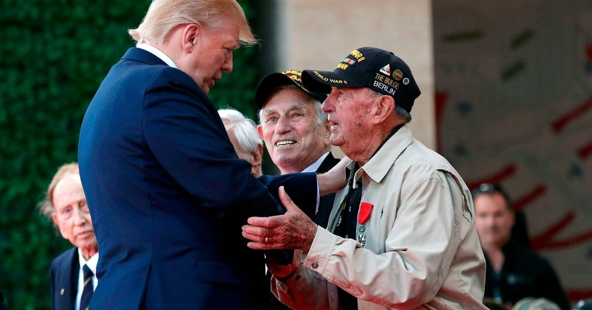President Donald Trump greet a U.S. veteran during a French-U.S. ceremony at the Normandy American Cemetery and Memorial.