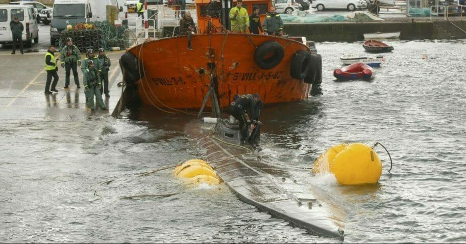 Spanish civil guard tow a sunken submarine