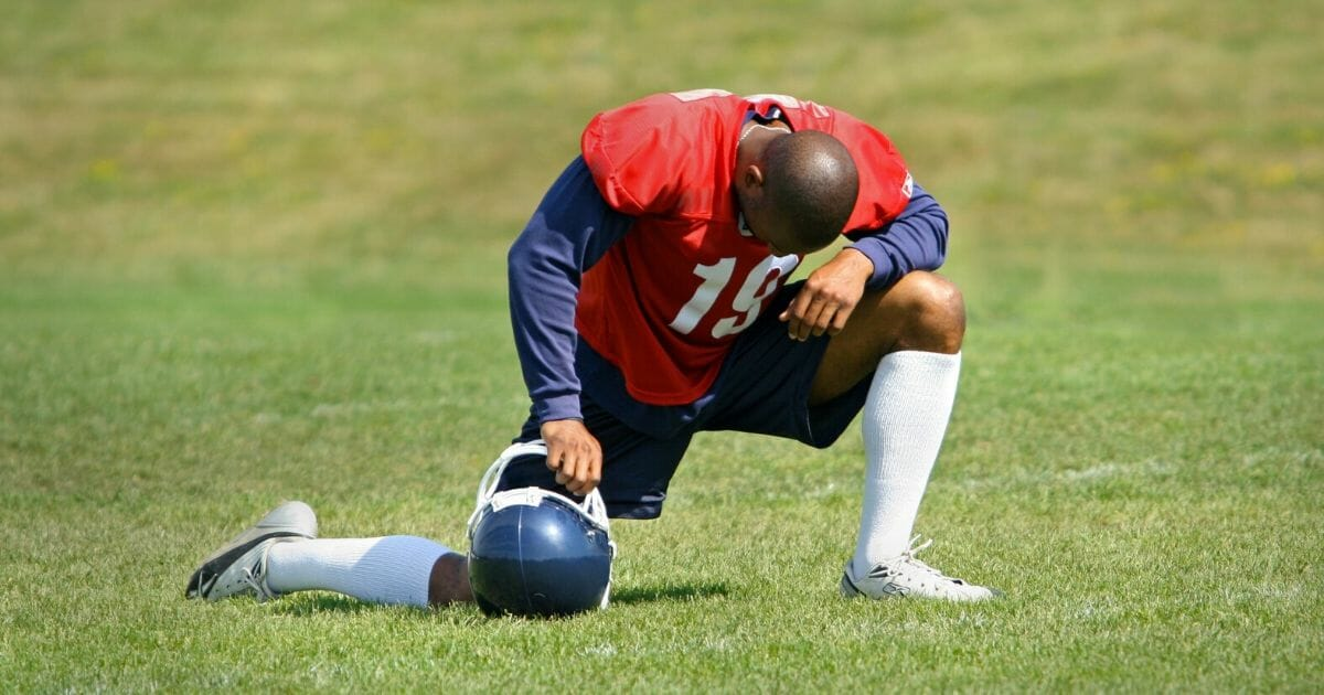A football player down on one knee.