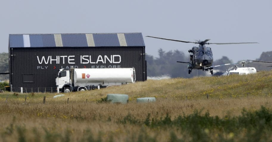 A Navy helicopter returns to Whakatane Airport following the recovery operation to return the victims of the Dec. 9 volcano eruption continues off the coast of Whakatane New Zealand, Friday, Dec. 13, 2019.