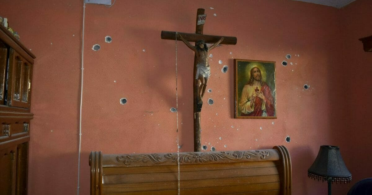 A wall of the room of a home is riddled with bullet holes