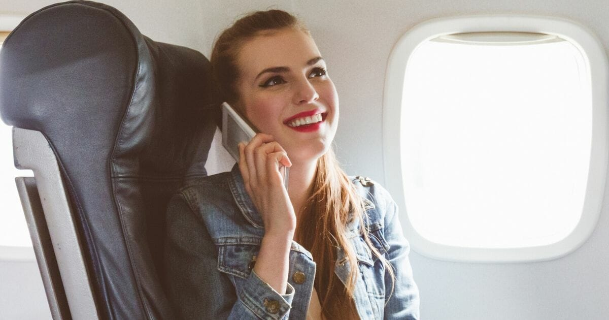 A passenger uses her cellphone during a flight.