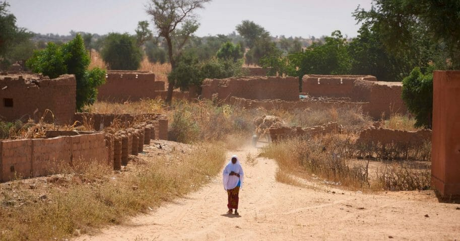 A Burkinabe woman observes the passage of French army vehicles in a village in northern Burkina Faso on Nov. 15, 2019.