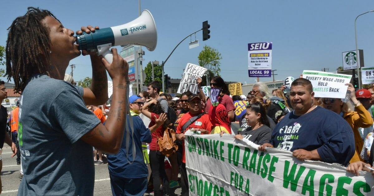 A man shouts into a megaphone during a demonstration for higher wages in Los Angeles on April 15, 2015.