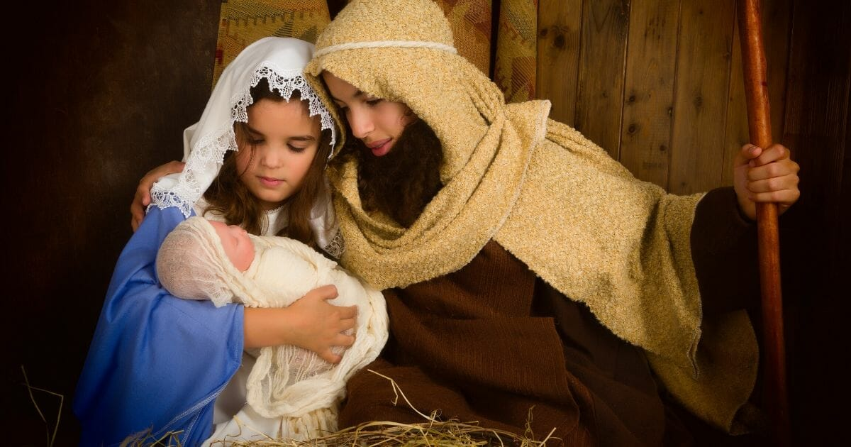 A Christmas Nativity scene featuring children and a doll.