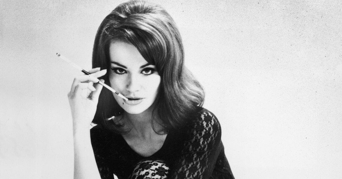 """French actress Claudine Auger smokes a cigarette in a promotional portrait for the James Bond film, """"Thunderball,"""" directed by Terence Young, in 1965."""