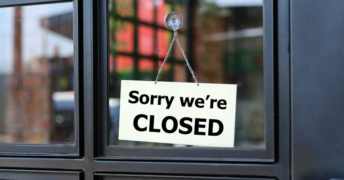 """""""Sorry We're Closed"""" sign hangs on door of small business."""