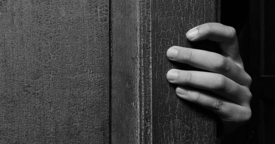 A hand around the edge of a door.
