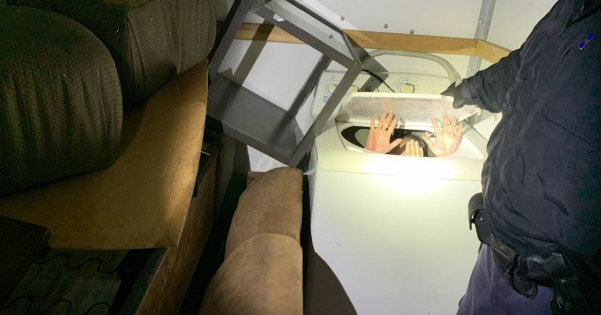 An immigrant is founding hiding in a washing machine inside a moving truck.