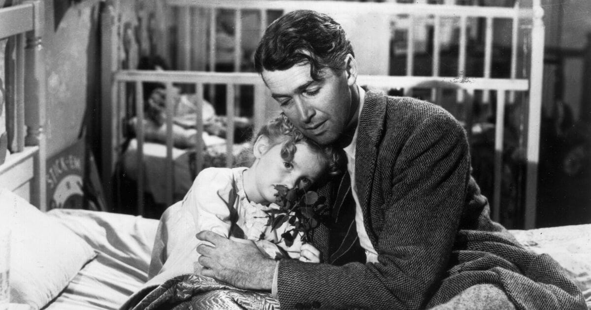 American actor James Stewart (1908 - 1997) as George Bailey, hugs actor Karolyn Grimes, who plays Zuzu his daughter, in a still from director Frank Capra's Christmas classic film, 'It's a Wonderful Life.'