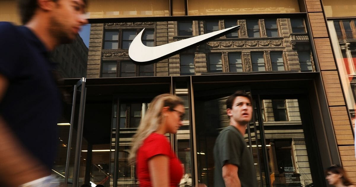 People walk by a Nike store in New York on Sept. 5, 2018.