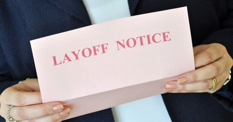 Female executive reading a layoff notice from her employer.