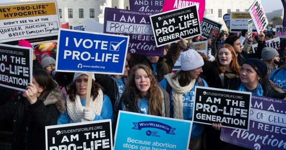 "Pro-abortion activists hold signs in response to pro-life activists participating in the ""March for Life,"" an annual event to mark the anniversary of the 1973 Supreme Court case Roe v. Wade, which legalized abortion in the U.S., outside the Supreme Court in Washington, D.C., on Jan. 18, 2019."