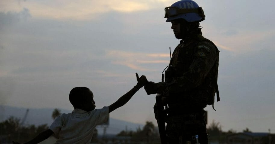 A Brazilian soldier with the MINUSTAH force greets a boy at a shantytown in Port-au-Prince on March 2, 2013.