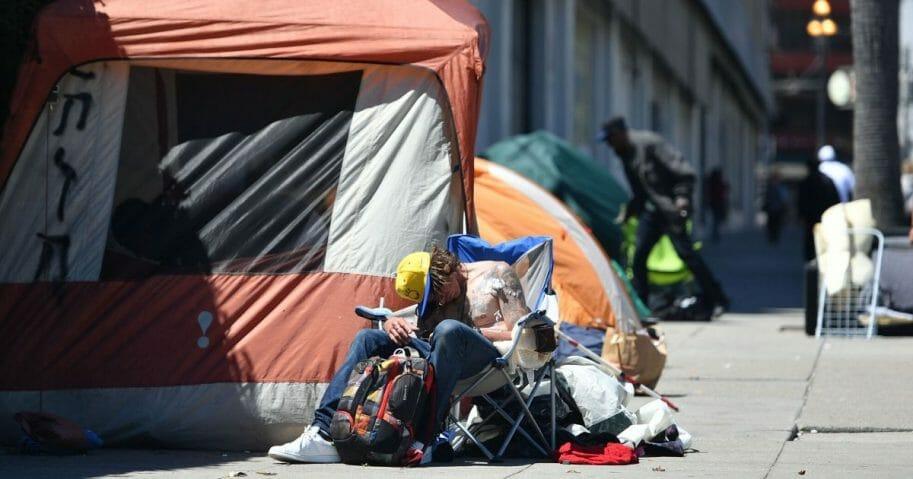 A homeless man sleeps on the street in San Francisco.