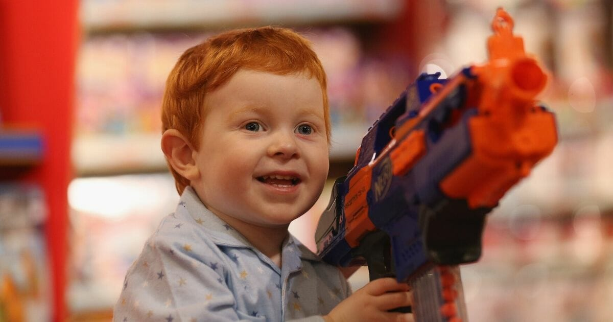 Tristan, aged 2, holds a 'Nerf Rapidstrike CS-18' toy gun in Hamleys toy shop on June 27, 2013, in London, England.