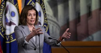 House Speaker Nancy Pelosi gestures to reporters with both arms during her news conference Thursday at the Capitol.
