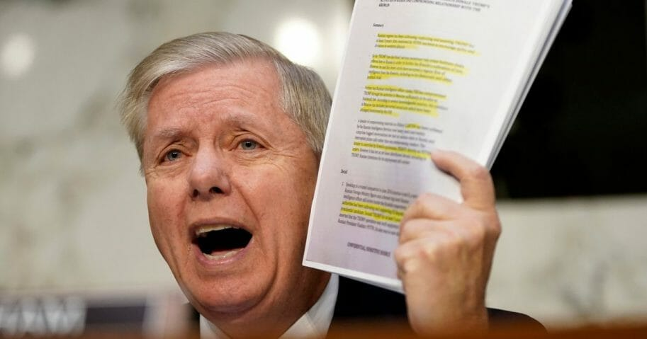 Senate Judiciary Committee Chairman Lindsey Graham holds up a copy of the Steele dossier as Michael Horowitz, inspector general for the Justice Department, testifies before the Senate Judiciary Committee in the Hart Senate Office Building on Dec. 11, 2019, in Washington, D.C.