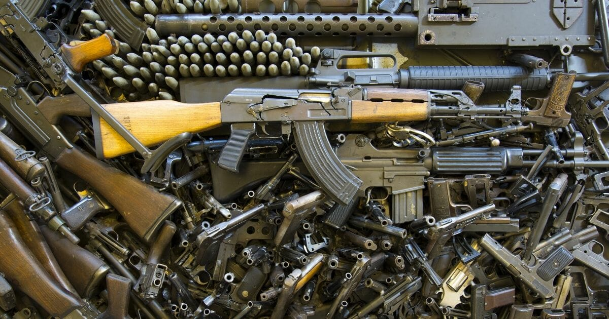 Stock image of a pile of firearms.