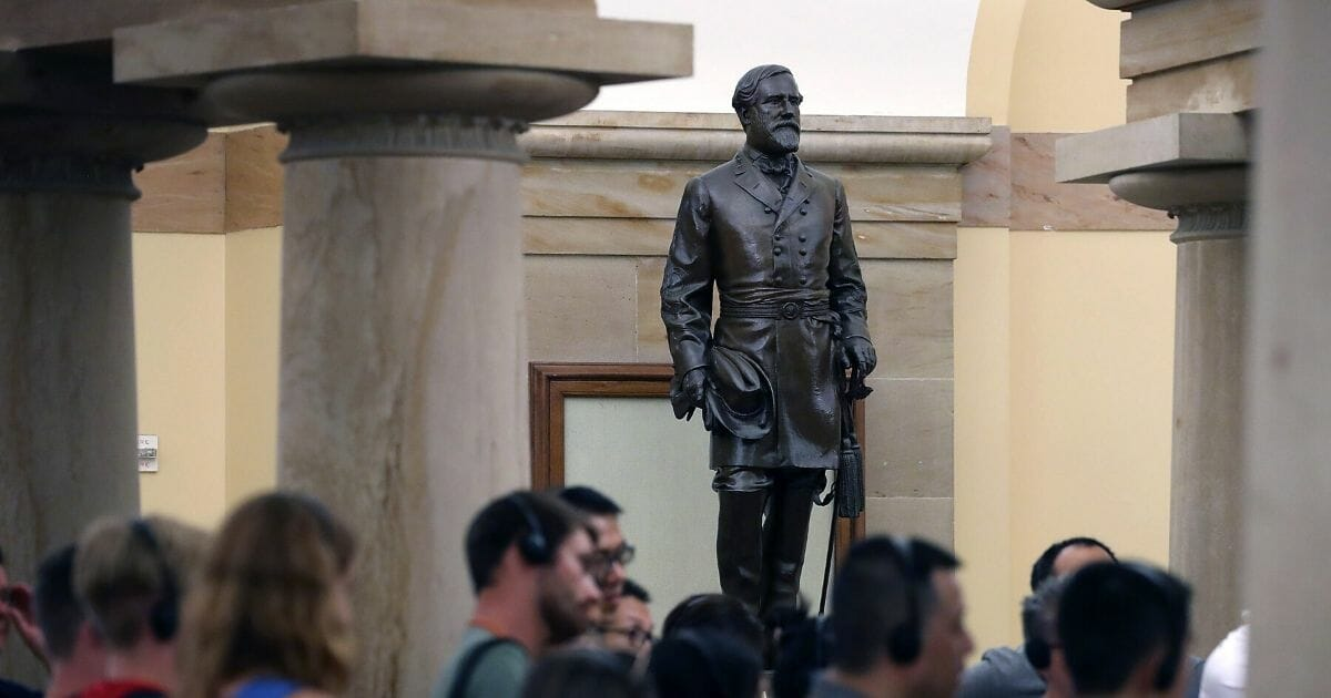 Tourists walk past the statue of Confederate General Robert E. Lee that is located inside the U.S. Capitol on Aug. 17, 2017, in Washington, D.C.