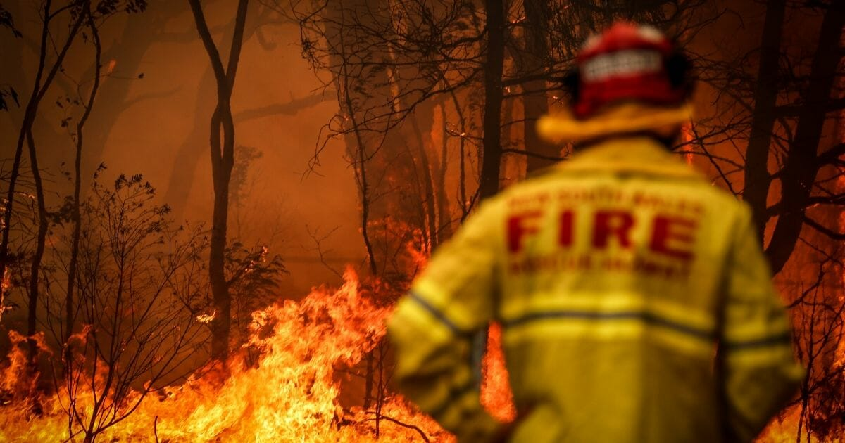 A firefighter watches a wildfire burning near homes on the outskirts of the town of Bilpin on Dec. 19, 2019, in Sydney.
