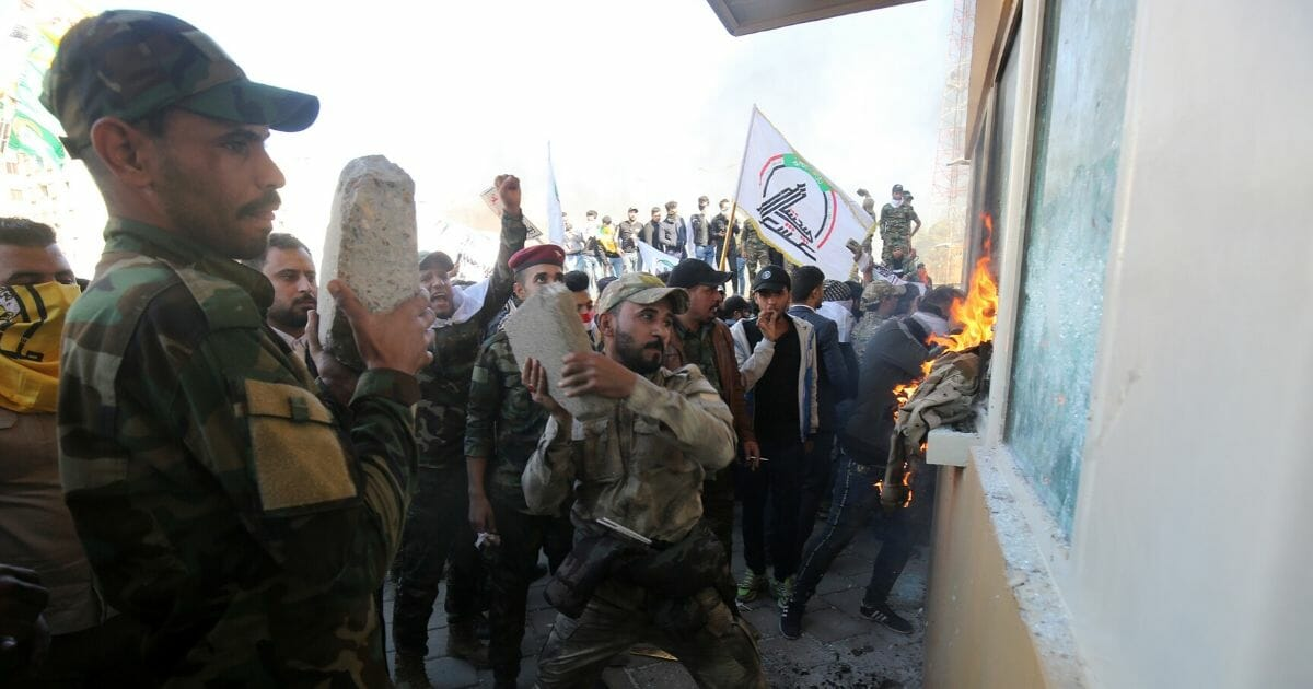 Members an Iranian backed militia smash the bullet-proof windows of the U.S. Embassy in Baghdad with concreteblocks on Tuesday. President Donald Trump blamed Iran for the attack, which as left the embassy under seige by pro-Iranian demonstrators.