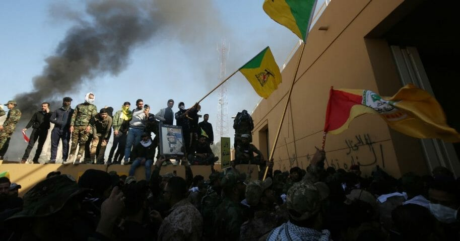 Smoke billows from a burning guard building at the entrance of the U.S. Embassy in Baghdad as thousands of Iraqi protesters breach the outer wall of the embassy grounds on Tuesday.
