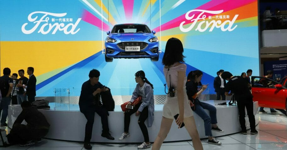 Attendees visit the Ford booth during the Auto China 2018 show held in Beijing on April 25, 2018.