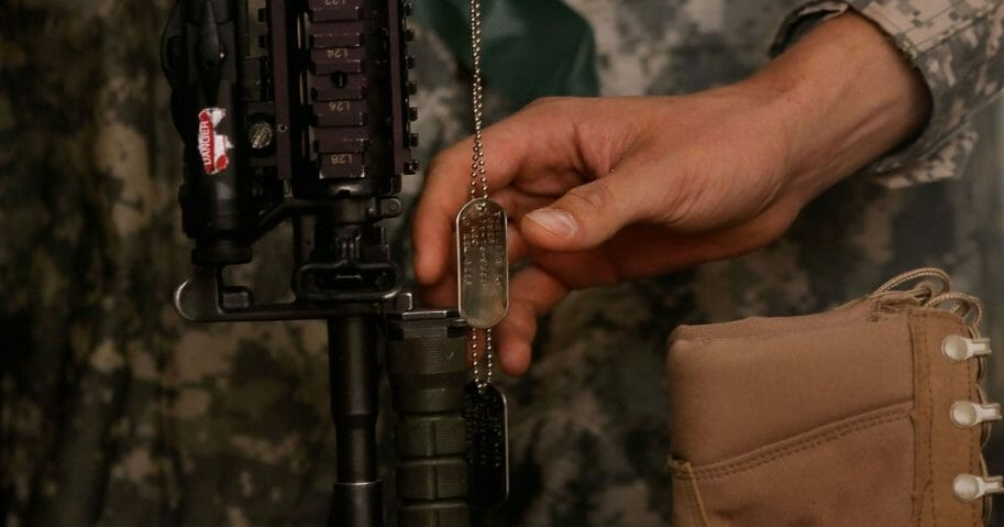 A U.S. soldier touches the dog tags of a slain comrade during a memorial service June 8, 2010, in Belanday, south of Kandahar, Afghanistan.