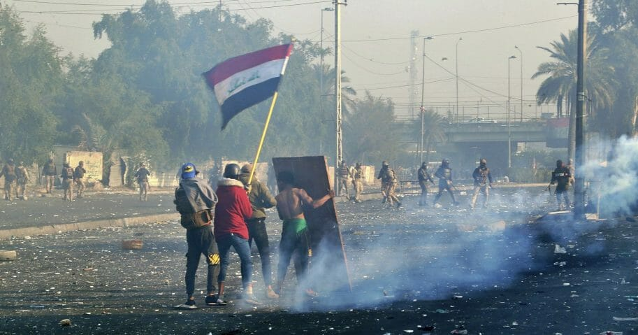 Protesters wave the Iraqi national flag as security forces fire tear gas during an ongoing protest in central Baghdad on Jan. 20, 2020.