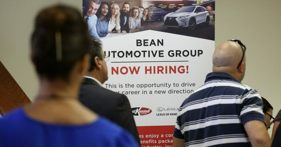 In this Sept. 18, 2019, file photo, people stand in line to inquire about jobs available at the Bean Automotive Group during a job fair in Miami.