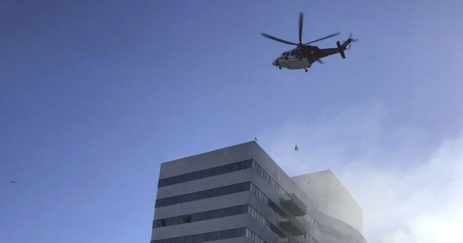 A helicopter flies over a residential building on fire in Los Angeles on Jan. 29, 2020.