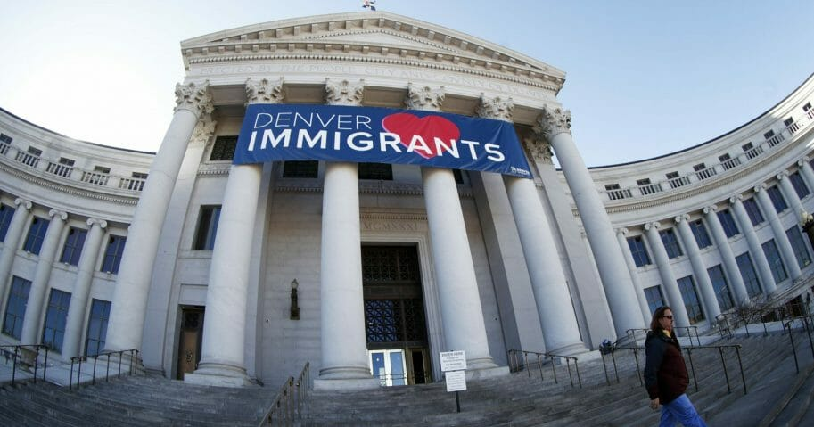 In this Feb. 26, 2018, file photo, a banner to welcome immigrants is viewed through a fisheye lens over the main entrance to the Denver City and County Building in Denver. U.S. Immigration and Customs Enforcement has subpoenaed Denver law enforcement for information on four foreign nationals wanted for deportation and could expand the unusual practice to other cities, an escalation of the conflict between federal officials and so-called sanctuary cities.