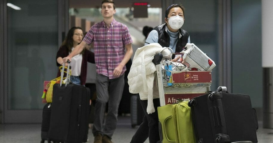 A woman wears a mask following the outbreak of coronavirus as people arrive from the International terminal at Toronto Pearson International Airport on Jan. 25, 2020.