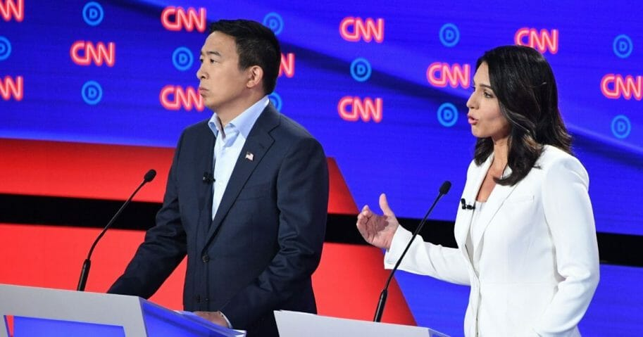 Democratic presidential hopefuls entrepreneur Andrew Yang, left, and Rep. Tulsi Gabbard of Hawaii speak during the second round of the second Democratic primary debate of the 2020 presidential campaign season hosted by CNN at the Fox Theatre in Detroit, Michigan, on July 31, 2019.