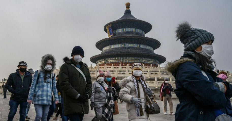 Visitors wear masks to protect themselves from coronavirus as they tour the grounds of the Temple of Heaven in Beijing on Jan. 27, 2020.