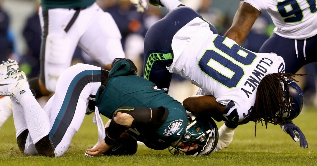 Quarterback Carson Wentz of the Philadelphia Eagles is hit by Jadeveon Clowney of the Seattle Seahawks during the wild-card playoff game Jan. 5, 2020, at Lincoln Financial Field in Philadelphia.